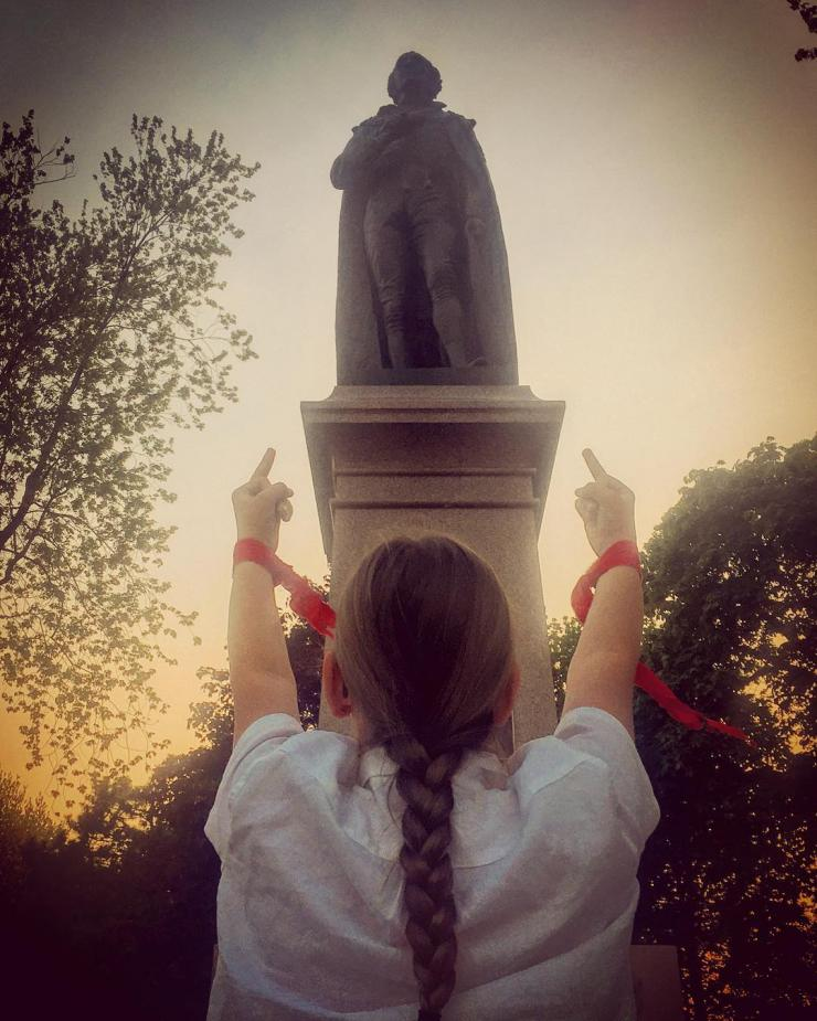 Woman with red wristbands flipping off a statue