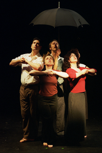 a group of actors under an umbrella on stage