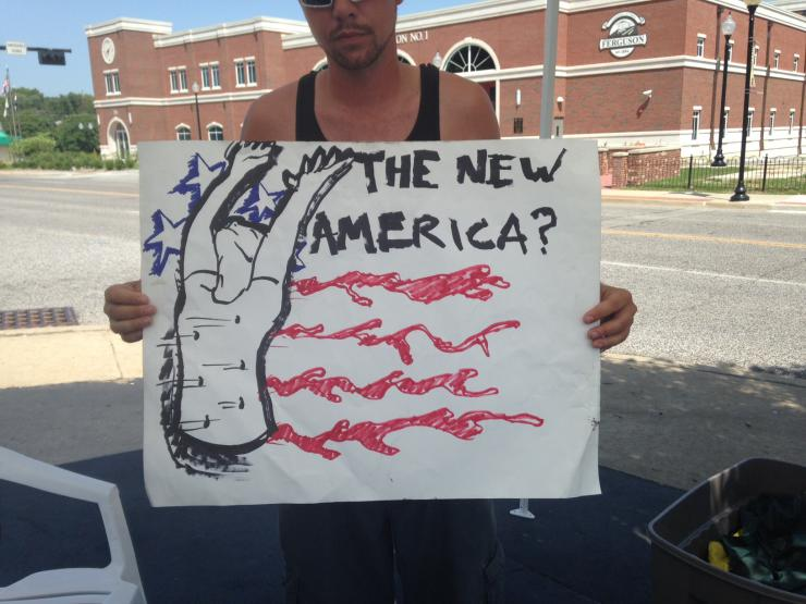A man holding a protest sign