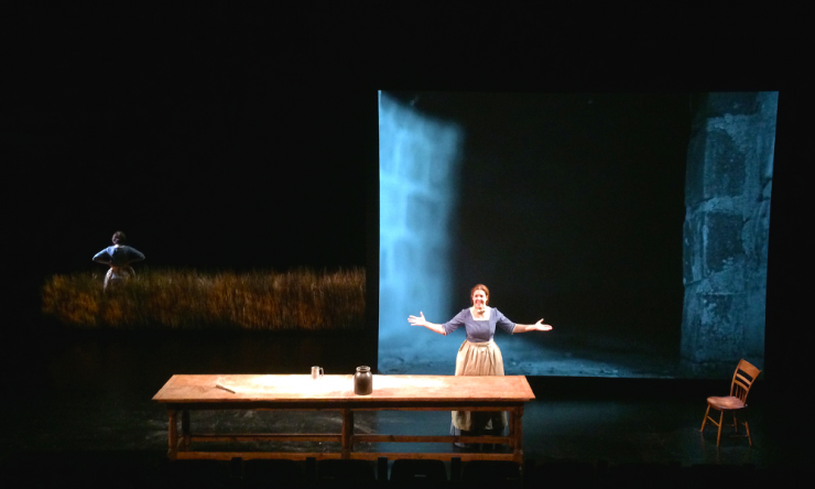 an actress at a table on stage
