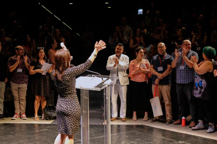A woman stands at a podium on stage as people in the audience applaud.