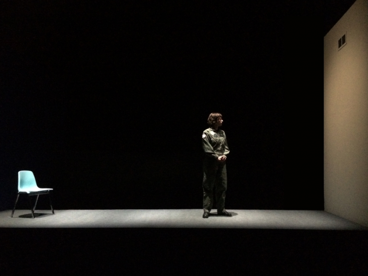 an actress alone on a blank stage