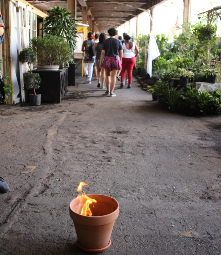 a group of people walking away from a burning plant