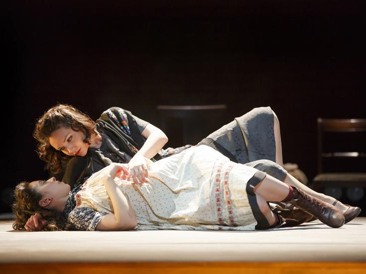 Two female actors lie together on stage