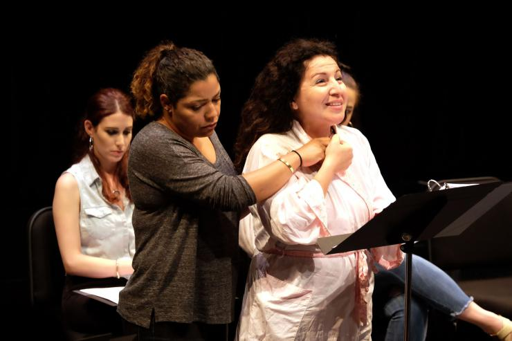 Two women embrace on stage in front of a music stand.