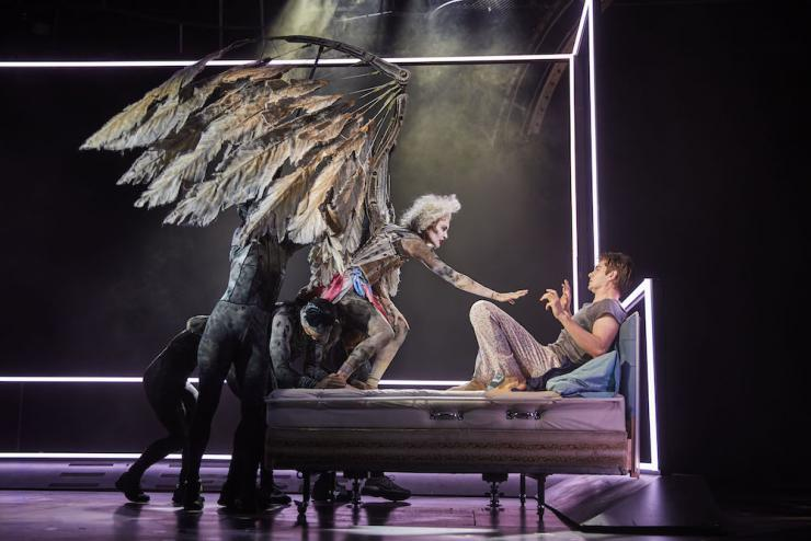 An actor wearing large wings hovers over another actor lying in a hospital bed