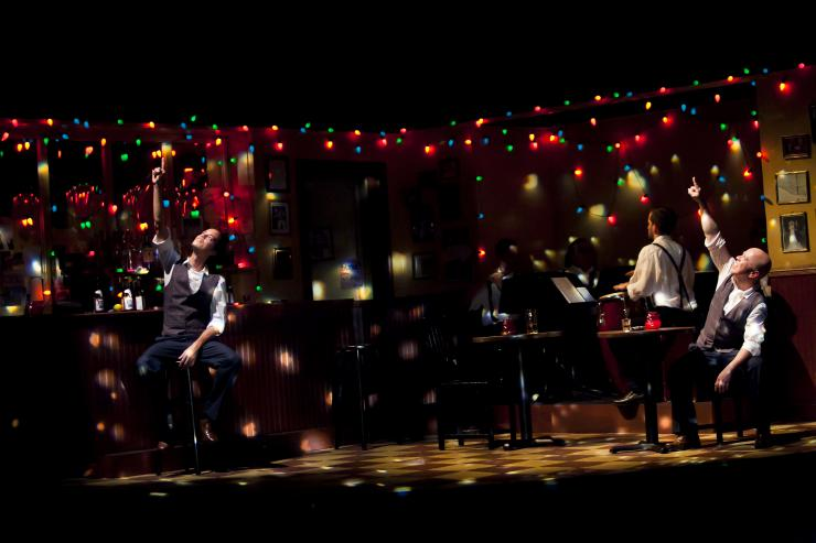 two actors on stage surrounded by colored lights
