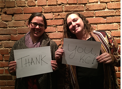 two women posing with thank you cards