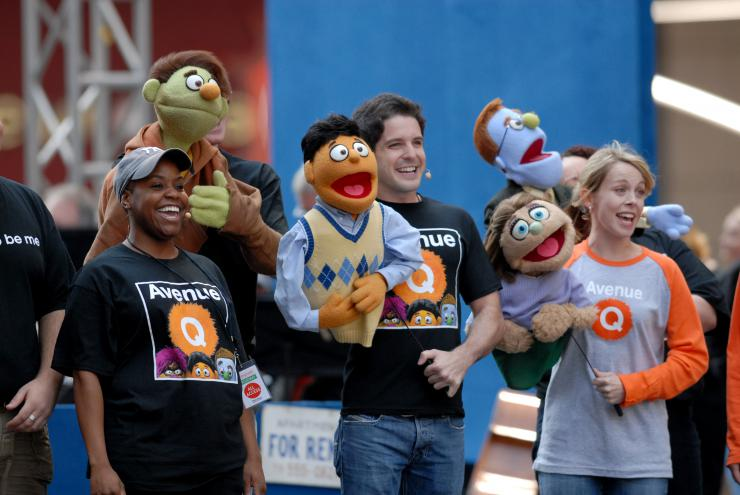 actors with puppets performing at a parade