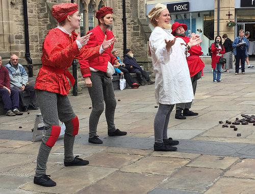 4 actors in costume performing outside