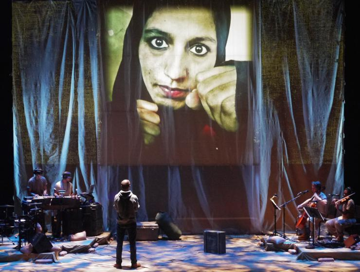 An actor with projections and a band on stage
