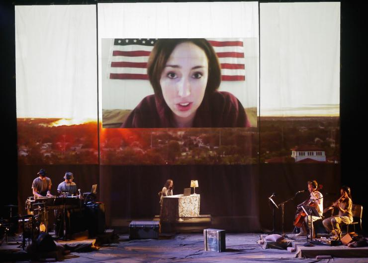 an actor with projections and band on stage