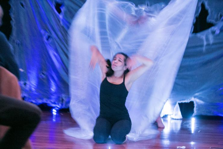 an actress performing in front of a white flowing tarp