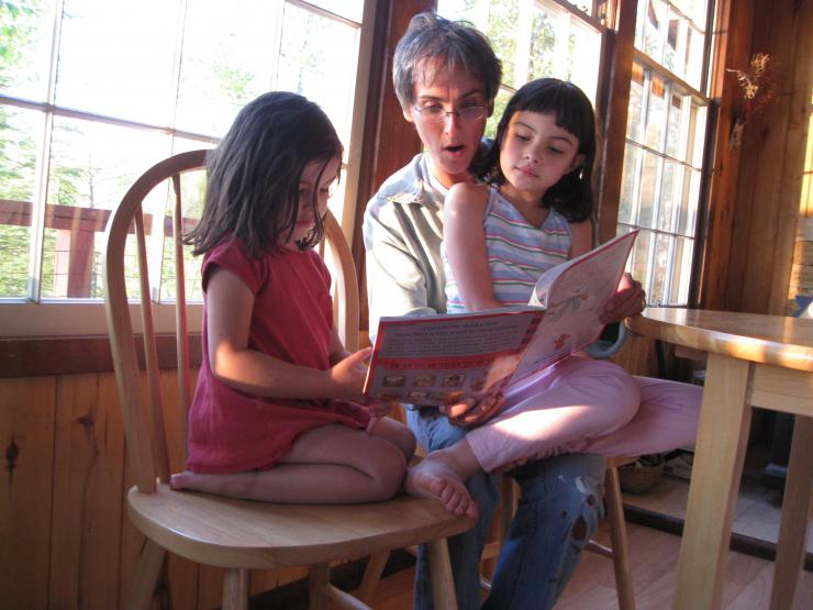 woman reading to two children