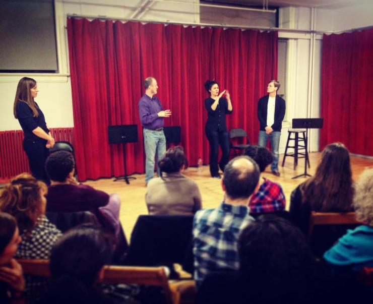 four people giving a speech in front of an audience