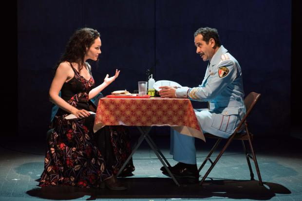 two actors at a table on stage