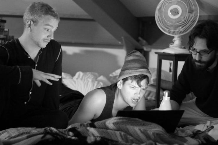 three men discussing around a computer