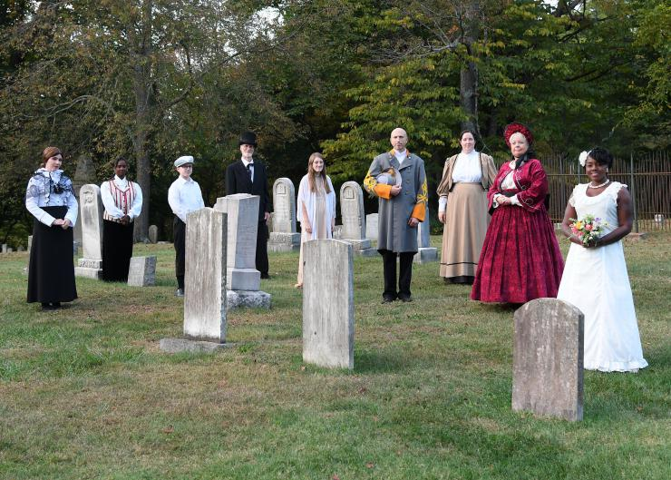 actors in costume on a cementary