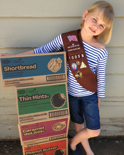 Girlscout standing next to a stack of boxes of cookies