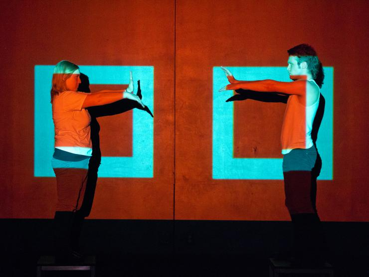 two actors performing in front of light rectangles