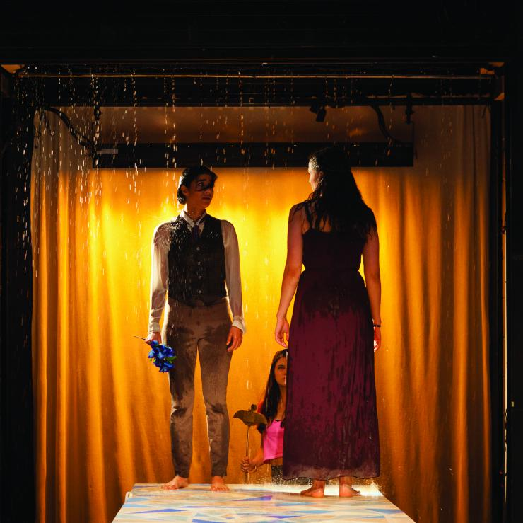 """two actors on stage in a """"rainshower"""""""