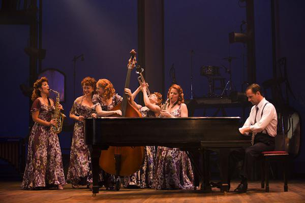 a group of actresses and an actor playing music on stage