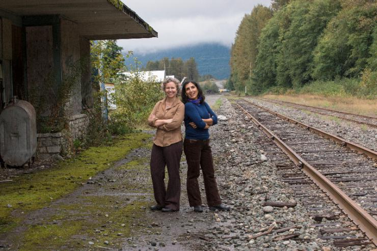 two women posing on train tracks