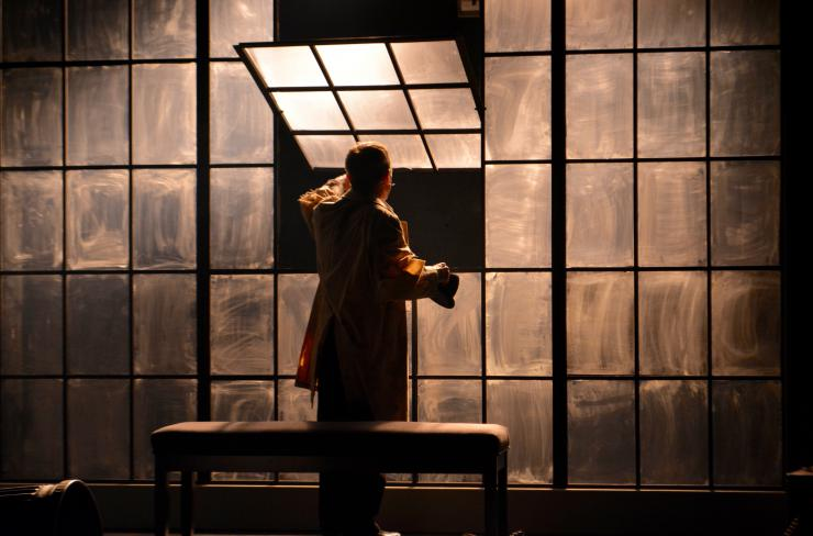 An actor at a window on stage