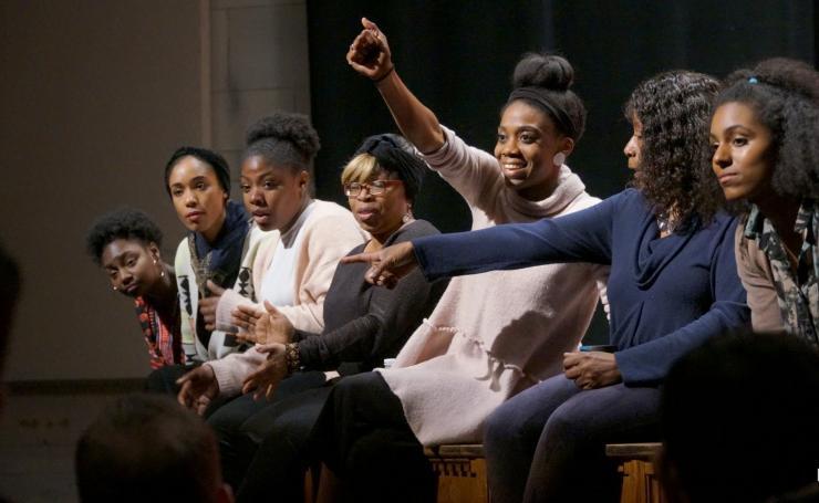 seven black women sitting onstage