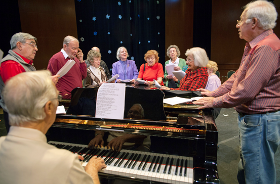 a group of seniors standing around a piano singing
