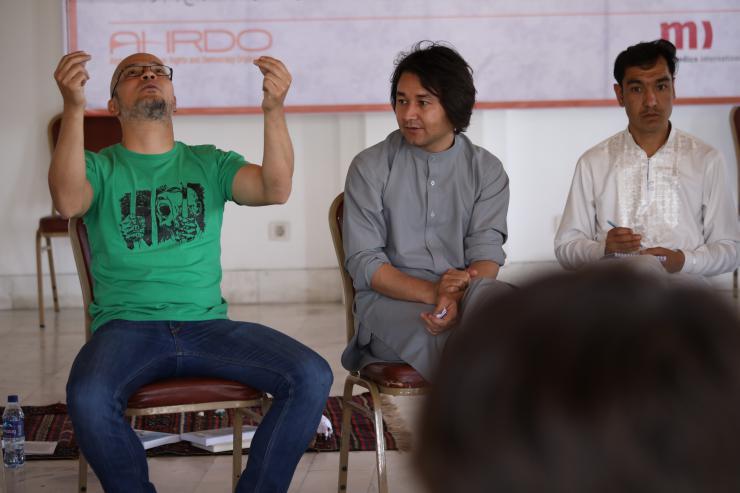 Three men sitting on a panel