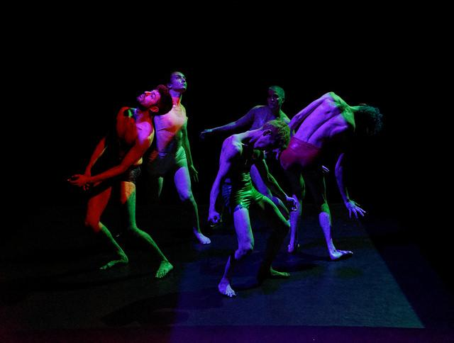 five performers dance in colored light