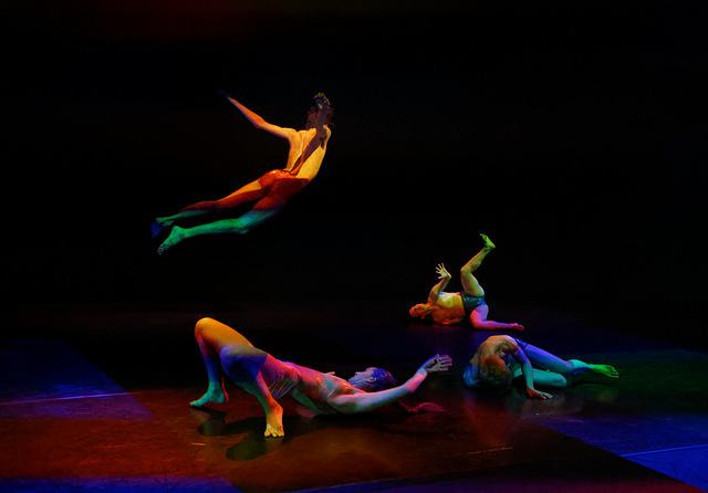 performers dance in colored light