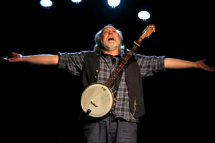 Actor holding out arms, wearing a banjo