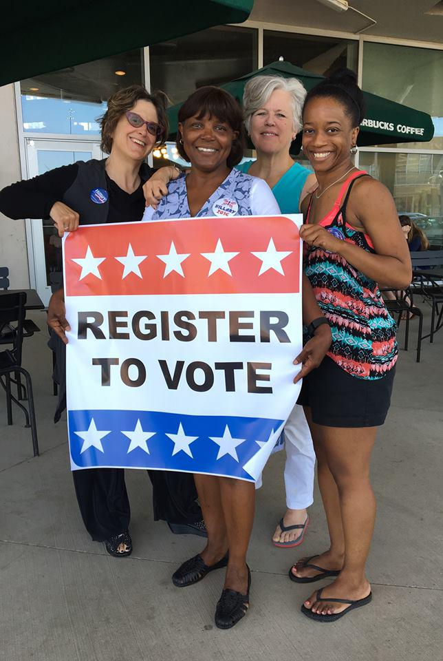 "women holding a ""register to vote"" sign"