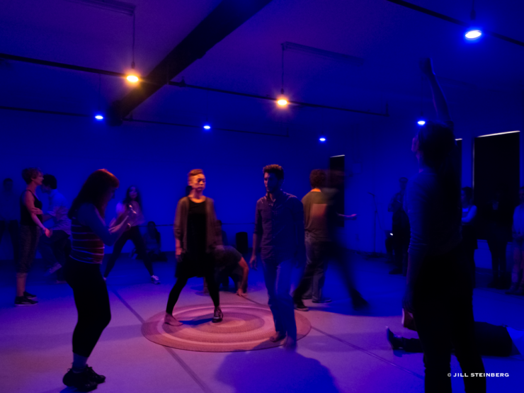 actors walking in a dimly lit room