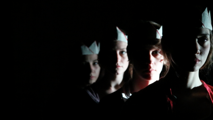 a group of actors wearing crowns