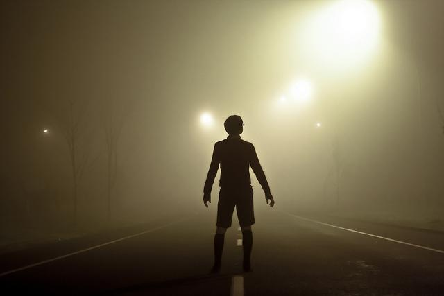 a person looking down a road into fog