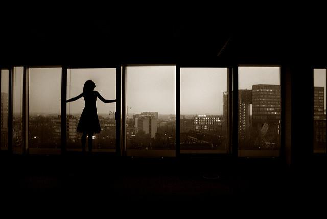 girl silhouetted at a window
