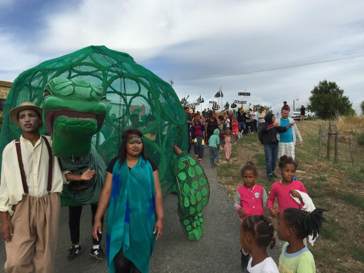 a group of people marching with a tortoise puppet