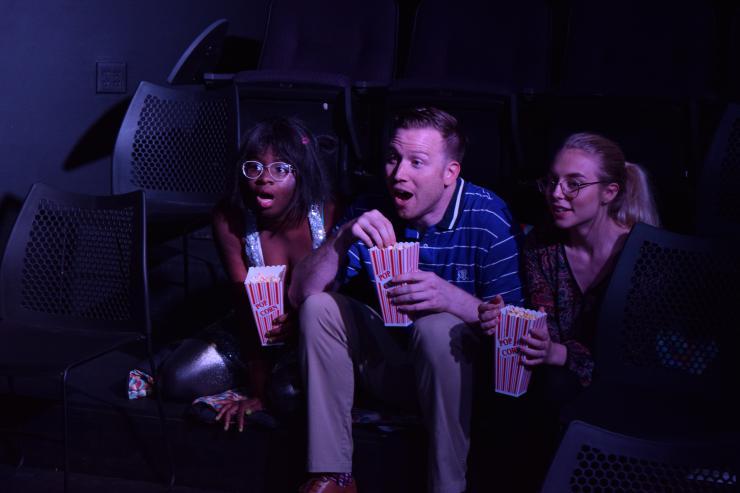 three performers onstage eating popcorn