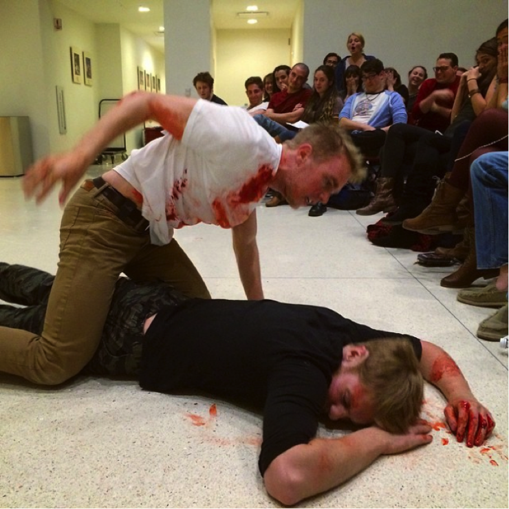 One bloody actor on top of another bloody actor in a fight scene