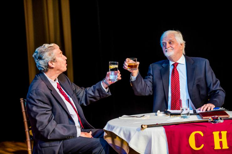two actors toasting on stage