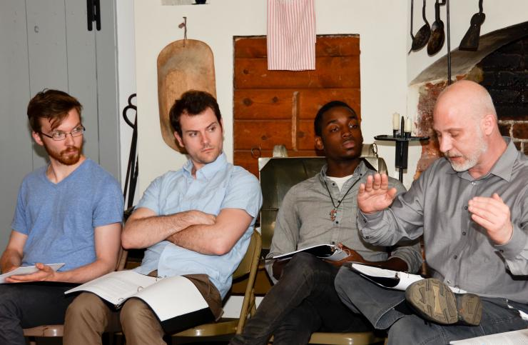three men listening to another man talk