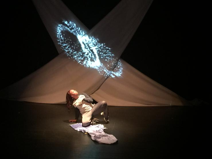 an actress performing in front of a projection