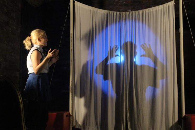 an actress performing in front of a silhoutte