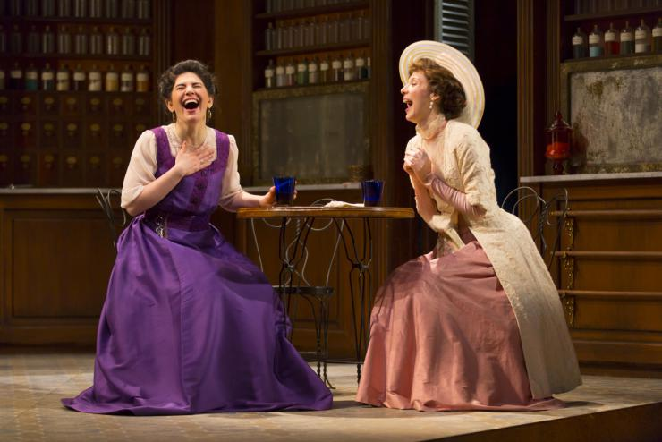two women in period costumes laughing on stage