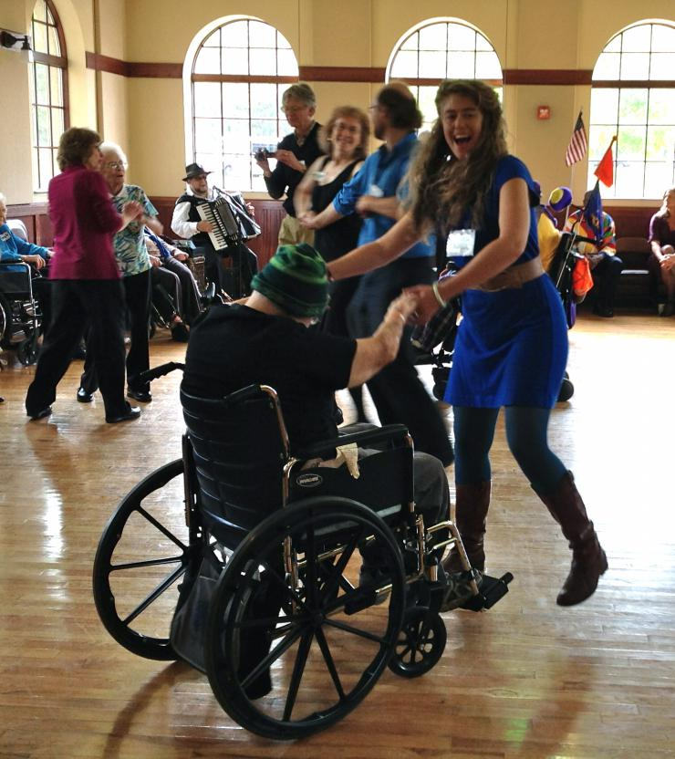 a woman dancing with someone in a wheelchair