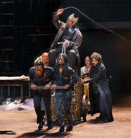 a group of actors carrying someone on stage
