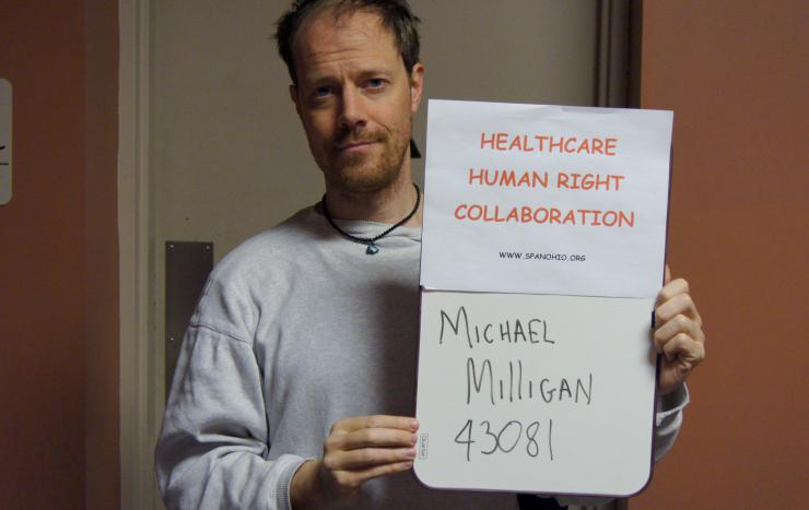 Michael Milligan holding a sign saying: Health Care Human Right Collaboration